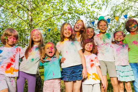 Big group of age-diverse kids, smeared with colored powder, standing together in a row outside in summer Stock Photo