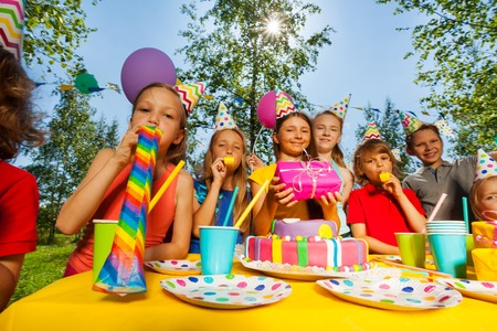 birthday party kids: Big group of happy kids in party hats blowing whistles at outdoor birthday party Stock Photo