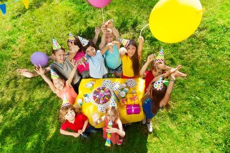 Bovenaanzicht van lachende kinderen staan rond de tafel met verjaardagstaart, wuivende handen en ballonnen, in de openlucht party Stockfoto