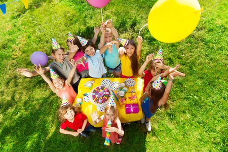 Top view of laughing kids standing around the table with birthday cake, waving hands and balloons, at the outdoor party Imagens