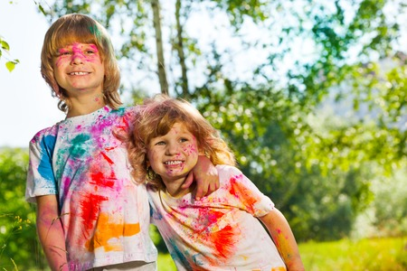 multiple stains: Close-up portrait of two funny age-diverse boys smeared with colored powder on Holi festival