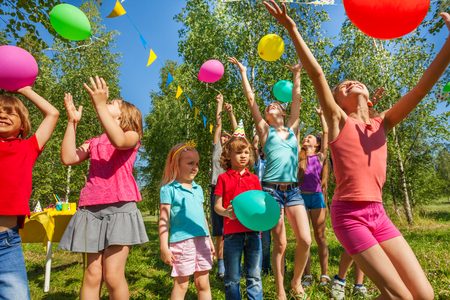 Happy age-diverse kids catching colorful balloons and playing outside in summer