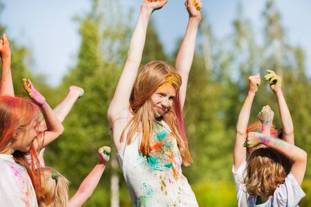 kids hand: Happy young girl, smeared with colored powder, dancing on Holi color festival Stock Photo