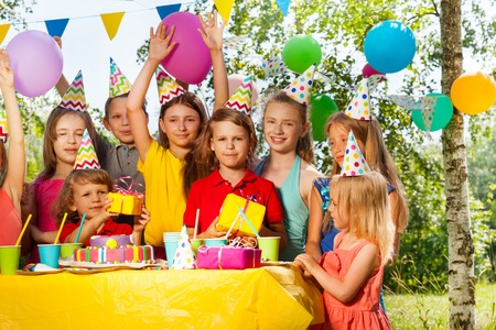 birthday party kids: Group of happy kids in party hats congratulating birthday boy at the outdoor party