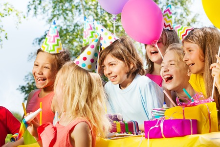 Group of happy kids having fun at outdoor Birthday party, side view
