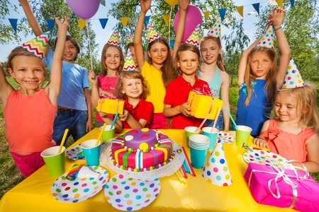 birthday party kids: Big group of happy smiling kids in party hats at the outdoor birthday party