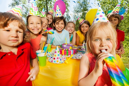 birthday party kids: Happy age-diverse kids having fun with bright party whistles at the outdoor birthday party