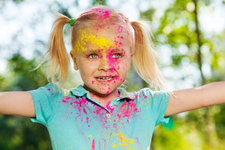 Close-up portrait of happy little girl with face smeared with colored powder