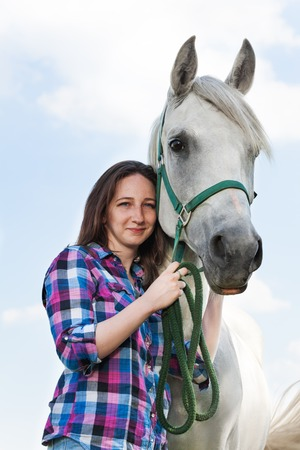 bridle: Portrait of beautiful young woman with her lovely white horse posing against blue sky Stock Photo