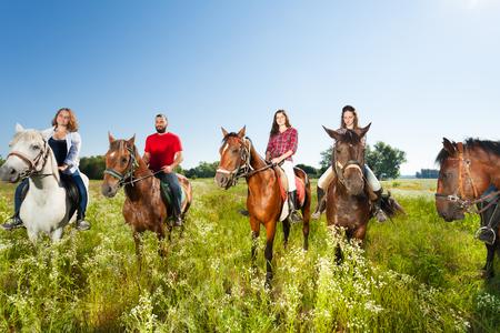champ de fleurs: Un grand groupe d'équitants jouit de chevaux dans un champ d'été