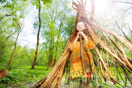 Portrait of happy girl playing Red Indian, standing next to the wooden wigwam, in the forest at sunny day