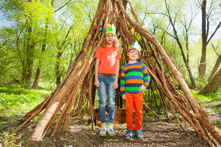 Portrait of happy boy and girl in Injuns headdresses, standing next to the wigwam made of branches in the forest Stock Photo
