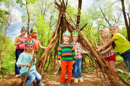 Portret van gelukkige jonge geitjes in kostuums Injun's, het bouwen van wigwam van takken in het bos