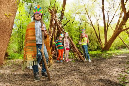 演奏红色印地安酋长的逗人喜爱的男孩画象与他的朋友在森林里