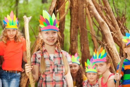 Portrait of smiling girl in Injuns costume playing with her friends in the forest