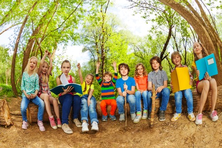 Big group of happy kids, sitting in a row outdoor on the log and reading books in the summer camp