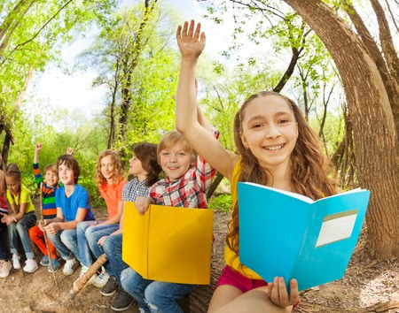 Portrait of happy girls and boys, reading books outdoor at sunny day