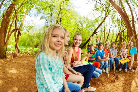 Big groupe d'enfants heureux, assis sur une bûche dans le camp d'été, la lecture de livres et d'élever leurs mains vers le haut