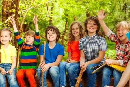 campamento: Retrato de niños exploradores felices y Exploradoras que se divierten, sentado en el registro, en el campamento de verano al aire libre Foto de archivo