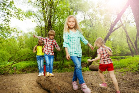 Happy kids walking on a log and balancing one by one in summer forest
