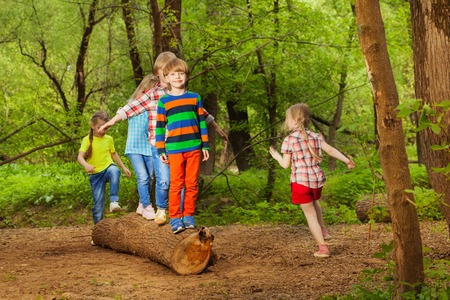 Portrait of Cute little boys and girls walking on trunk of tree in summer park