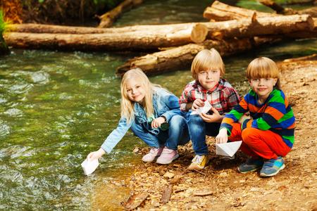 夏に川の土手でペーパー ボートで遊ぶ 3 つの幸せな子供