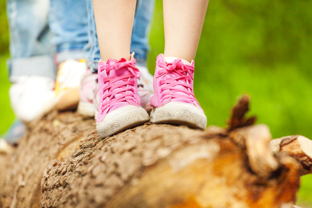 Close-up picture of childrens feet in pink sneakers standing on a log