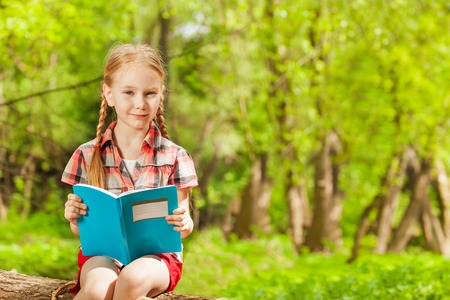 diligente: Retrato de colegiala diligente lectura de un libro, sentado sobre un tronco en el parque de verano