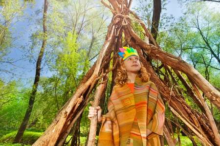 Portrait of cute girl in Indian costume playing next to a hut, made of branches Stock Photo