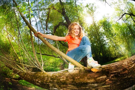 Portrait of teenage cute girl sitting on trunk of fallen tree and holding on to a branch in the forest