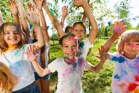 dye powder: Portrait of bright kids smeared in colored powder at the outdoor color festival in summer