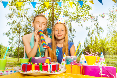 Portrait of two happy young girls playing with party blowers, standing next to the birthday cake, at the outdoor birthday party Stock Photo