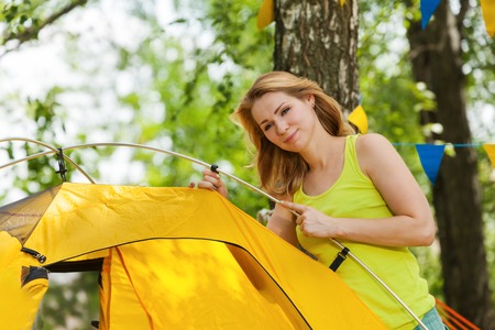 pitching: Portrait of beautiful happy young woman putting up yellow tent in the woods in summer Stock Photo