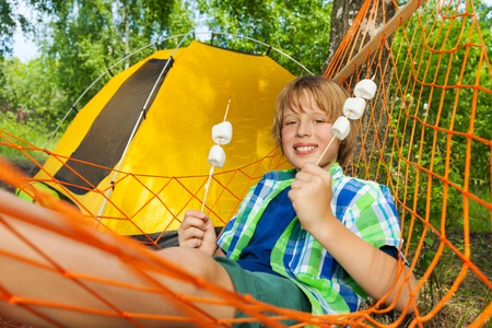 campsite: Portrait of happy smiling boy with roasted marshmallow on sticks, relaxing in a hammock next to the tent
