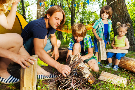 Portrait of young father teaching his three age-diverse kids making a camp fire in the forest Zdjęcie Seryjne