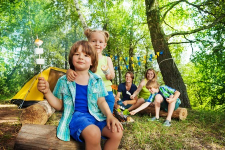 Portrait of two happy kids, three years old boy and girl, holding roasted smors on sticks at the campsite Stockfoto