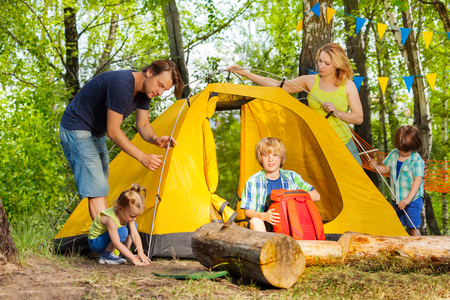 Happy big family, parents and three kids, putting up a tent together in the woods