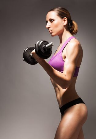 Strong fit young woman exercising with dumbbell side view dramatic portrait Stock Photo