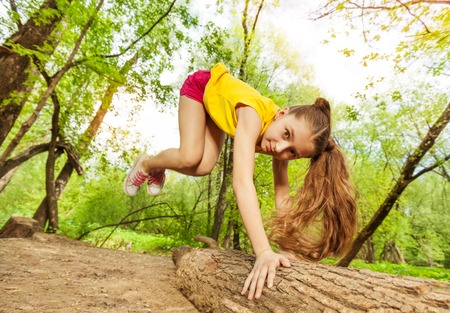 Close-up portrait of cute girl jumping over the log in the forest Reklamní fotografie - 65987249