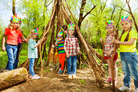 Happy boys and girls in Injun's headdresses, building wigwam of branches in the forest 스톡 콘텐츠