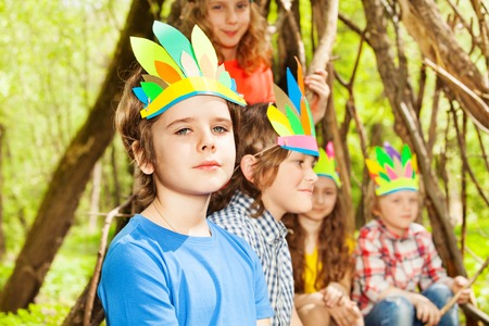 Close-up portrait of cute boy in Injuns headdress playing with his friends in the forest