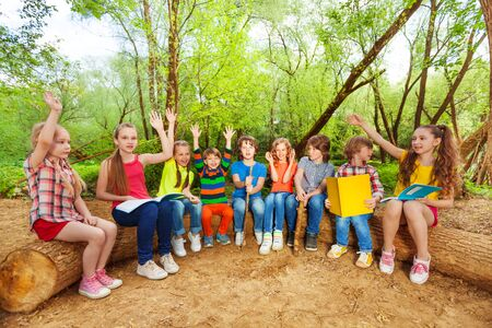 log book: Big group of kids, reading books in the forest, sitting in a row on the log with their hands up