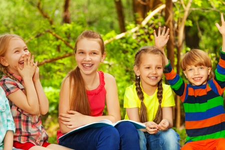 Portrait of four cute kids having fun in the summer forest