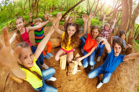 niños jugando en el parque: Grupo de niños felices levantando sus manos en el bosque en verano Foto de archivo
