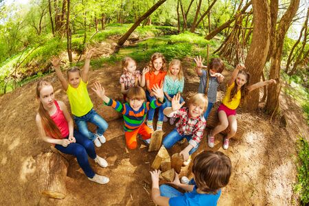 Big group of cute kids having fun with their hands up in the forest in summer