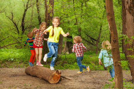 Portrait of cute little kids playing on a log, walking, jumping and balancing in the forest 免版税图像