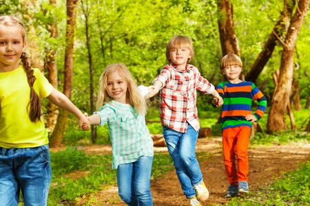 Portrait of four happy friends running holding their hands in the forest Stock Photo