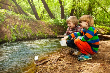 Vue latérale portrait de deux petits amis à jouer avec des navires de papier au bord de la rivière en été