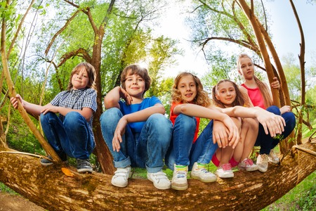 Close-up portrait of five kids sitting in line on trunk of fallen tree in summer forest Фото со стока
