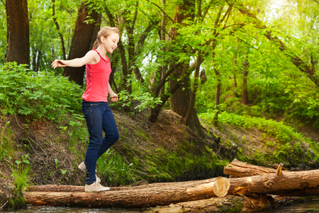 Side view portrait of teenage girl crossing a river in the forest to reach other side